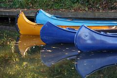 Canoes and reflection on water. Colorful canoes and their reflection on water in autumn Stock Photography