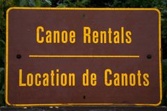 Canoes Rental sign written in english -french location de canots in Ontario algonquin national park canada for rent sign Royalty Free Stock Photos