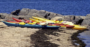 Canoes on the rocky beach. A picture of several colorful canoes, left on a rocky beach in Boothbay Harbor, Maine, USA Royalty Free Stock Image