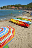 Collioure Southern France. A colourful striped sun shade and canoes on a beach in the foreground with the ocean and coastline behind. Copyspace royalty free stock images