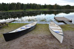 Canoes by the side of a lake. Scenic view of a lake in the countryside with canoes moored in the foreground Stock Photography