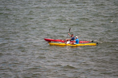 Canoes with unidentified people rowing in the sea Royalty Free Stock Image