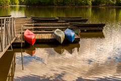Canoes upside down on a dock on a lake stock images