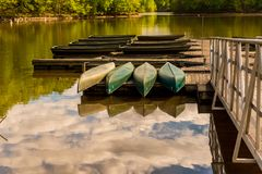 Canoes upside down on a dock on a lake royalty free stock images