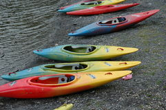 Canoes by the waterfront. A series of colorful canoes by the waterfront just before some sports lessons Royalty Free Stock Image