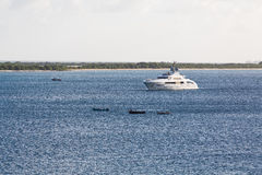 Canoes by White Luxury Yacht on Blue Water Stock Photography