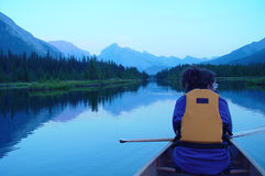 Canoing in the Canadian Rockies. Woman canoing at sunset on a mountain Royalty Free Stock Image