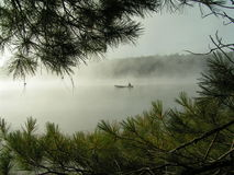 Canoing on misty lake royalty free stock images