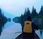 Canoing through a purple haze. Canoing in a mountain lake at dusk, purple sky from forest fire smoke, reflections in water Royalty Free Stock Image