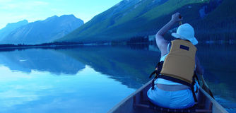 Canoing at sunset. Woman canoing at dusk on a mountain Royalty Free Stock Images