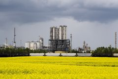 Canola and industrail palnt. Photo of an industrail plant with a canol field in front of it Royalty Free Stock Photos