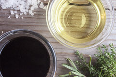 Canola oil and balsamico. Near thyme, rosemary and rock salt. On wooden background stock images
