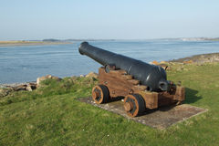 Canon. An historical black canon on a wooden trolley overlooking a narrow stretch of water Stock Photography