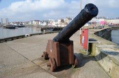 Canon antique de bateaux situé sur un quai avec un port dans Image stock