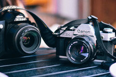 Canon Black and White Camera Besides Nikon Black Bridge Camera Royalty Free Stock Images