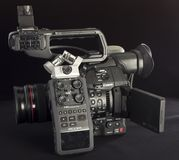 Canon C100 Mark II with audio recorder Zoom H6. Canon C100 Mark II and a digital audio recorder Zoom H6 on a black background. Perfect kit to record corporate Stock Photo