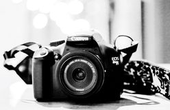 Canon camera. In black and white with a 24 mm lens and a strap on a table top in front of bokeh lights Royalty Free Stock Photos