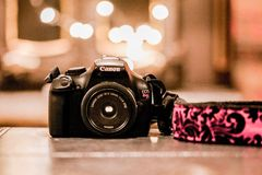 Canon camera with strap. Canon camera T3 with pink and black strap and a 24 mm lens sitting on table top in front of bokeh lights Stock Photo