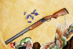 Canon du chasseur et des cartouches sur un tapis Images stock