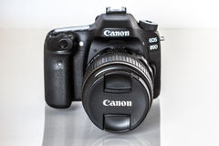 Canon EOS 80D DSLR camera. DSLR Camera - Canon 80D digital camera with lens on a reflective background Stock Images