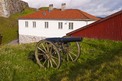 Canon and guard building. An old canon locaded on the Fredriksten fortress. In the backgroun are the old guard building Royalty Free Stock Photography
