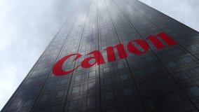 Canon Inc embleem op een wolkenkrabbervoorgevel die op wolken wijzen Het redactie 3D teruggeven Stock Fotografie