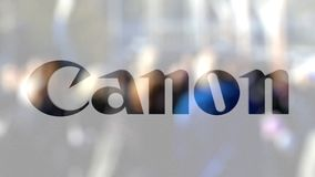 Canon Inc. logo on a glass against blurred crowd on the steet. Editorial 3D rendering. Canon Inc. logo on a glass against blurred crowd on the steet. Editorial stock video footage