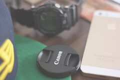 Canon Lens Cover Beside Gold Iphone 5s and Casio G Shock Chronograph Watch Stock Photo