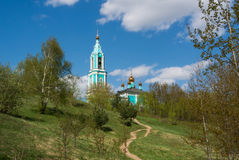 Canonic view of small russian ortodox church over the hill, beautiful summer landscape with trees and a path. Moscow, Russia Royalty Free Stock Photo