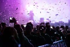 Canons de confettis jetant des confettis au-dessus de la foule faisante la fête Images libres de droits