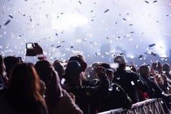 Canons de confettis jetant des confettis au-dessus de la foule faisante la fête Photographie stock libre de droits