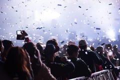 Canons de confettis jetant des confettis au-dessus de la foule faisante la fête Image libre de droits