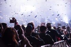 Canons de confettis jetant des confettis au-dessus de la foule faisante la fête Photo libre de droits
