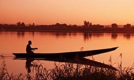 Canoo en la puesta del sol Imágenes de archivo libres de regalías
