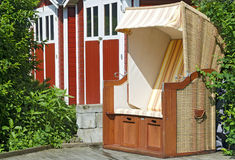 Canopied beach chair at a garden. Behind are red and white painted garden sheds Stock Photography