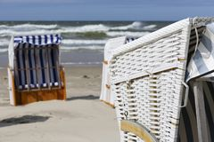 A canopied beach chairs, sandy beach in Kolobrzeg. Typical canopied beach chairs as seen in Kolobrzeg by the Baltic sea coast There are no people on the sandy Royalty Free Stock Photos