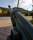Canopied cannon towards a green hill, the relic of the Second World War, the guard of the monument of the unknown soldiers fallen Stock Images