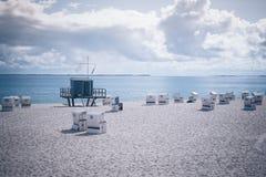 Canopied ligstoelen op zandig strand op het Eiland Sylt stock foto's