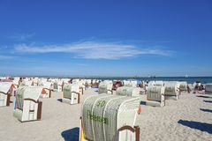 Beach in Grömitz. Canopied wicker beach chairs on the beach with the pier in the background Royalty Free Stock Images