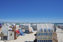 Beach in Grömitz. Canopied wicker beach chairs on the beach with the pier in the background Stock Image