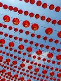 Many Lines of Chinese Red Lanterns hanging against a clear blue sky Stock Image