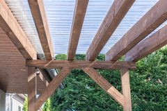 Canopy of a terrace made of wood and transparent corrugated sheets stock image