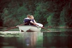 Canotaje de la muchacha y del muchacho y abrazo en el lago Foto de archivo libre de regalías
