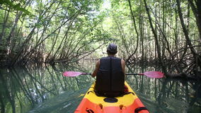canotaje del hombre en kajak a lo largo de la laguna
