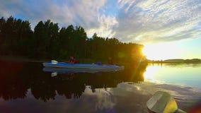 Canotaje en el río en la puesta del sol, gente que tiene resto después de remar metrajes