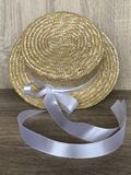Canotier straw hat with a white ribbon. Canotier hat Staw hat with a white ribbon. Wooden background in perspective Royalty Free Stock Image