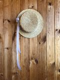 Canotier hat with a white ribbon on a wooden background. Canotier hat. Straw hat with a white ribbon on a wooden background Royalty Free Stock Photo