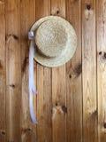 Canotier-Hut mit einem weißen Band auf einem hölzernen Hintergrund lizenzfreies stockfoto