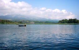 Canottaggio asiatico dell'uomo sul fiume al giorno Immagini Stock
