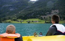 Canottaggio del figlio e del padre sul lago Immagine Stock